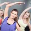 Three beautiful young woman doing aerobics exercises — Stock Photo #6476098