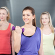 Three fit and beautiful young women lifting weights — Stock Photo