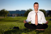 Barefoot businessman meditating — Stock Photo