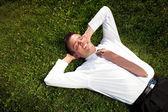 Предприниматель лежал в траве и расслабляющий — Стоковое фото