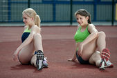 A couple of young female athletes stretching — Stock Photo