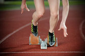 Action packed image of a female sprinter leaving starting blocks — Foto Stock