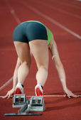 Muscular female sprinter at the starting line in starting blocks ready to b — Stock Photo