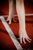 Female athlete's arms on the starting line — Stock Photo