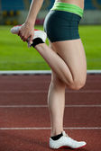 A female sprinter stretching — Foto de Stock