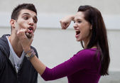Aggressive young woman about to punch her boyfriend — Stock Photo