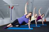 Group of three young women doing exercises in a fitness club — Stock Photo