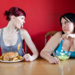 Skinny girl with a whole chicken teasing fat girl who's on a die - Stock Photo