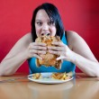 Happy overweight woman stuffing herself with chicken — Stock Photo