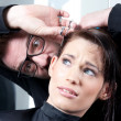 Mad hairdresser with a terrified customer - Stock Photo