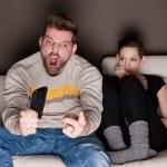 ein Mann, ein Spiel zu beobachten, während seine Freundin neben ihm sitzt gelangweilt — Stockfoto