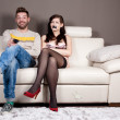 A happy man is watching TV in silence because he taped his girlfriend' — ストック写真