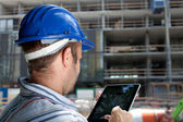 Construction specialist using a tablet computer — Stockfoto