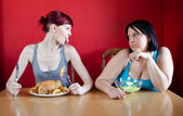 Skinny girl with a whole chicken teasing fat girl who's on a die — Stock Photo