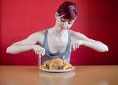 Enthusiastic skinny young woman about to eat a whole chicken — Stock Photo