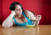 Unhappy overweight woman with her meal, a bowl with a few leaves — Stock Photo