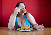 Overweight woman with a whole chicken on her plate stuffing herself — Stock Photo