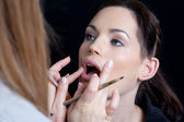 Professional make up artist applying make up to a fashion model/bride. — Stock Photo