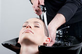 Young woman getting her hair washed at the hairdresser — Stock Photo