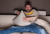 Un hombre mirando una película de terror. en el sofá. — Foto de Stock