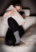 Beautiful young woman watching a horror movie alone — Stock Photo