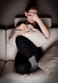 Una mujer joven atractiva mieda viendo una película de terror en casa sola. — Foto de Stock