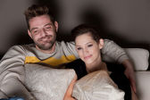 A young couple in love watching TV at home — Stock Photo