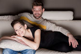 A couple watching TV on a sofa. — Stock Photo