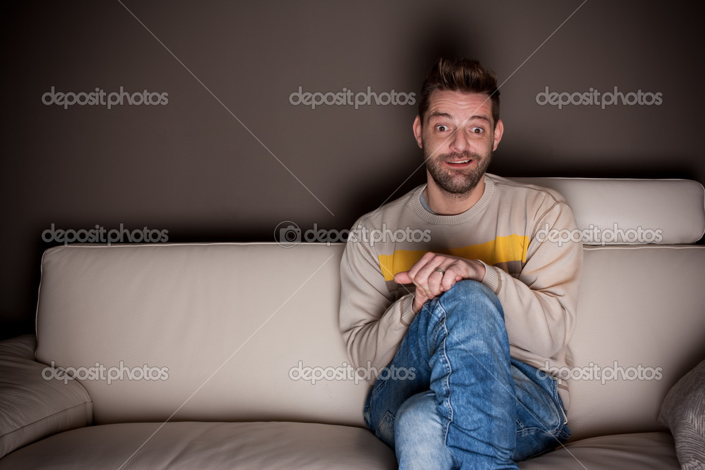 A man with crossed legs watching TV  — Stock Photo #6604479