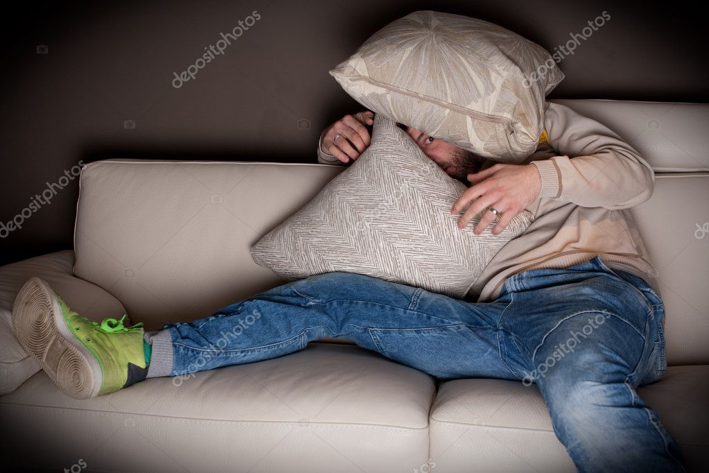 A very scared man watching a horror movie at home  — Stock Photo #6604490