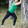 Woman stretching/warming up before running. Selective focus. — Stock Photo