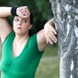 Exhausted overweight woman after a long run in the woods — Stock Photo