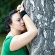 Exhausted overweight woman leaning on the tree and catching her — Stock Photo #6642913