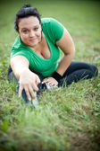 Happy overweight woman stretching in a park — Stock Photo