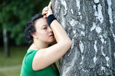 Exhausted overweight woman leaning on the tree and catching her — Stock Photo