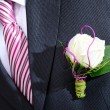 Groom in a wedding dress holding a white rose — Stock Photo