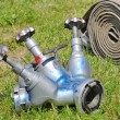 Valves and fire hoses in action on grass — Stock Photo