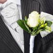 Groom in a wedding dress holding a white rose — Stock Photo #6686613