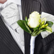 Stock Photo: Groom in a wedding dress holding a white rose