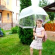 Stock Photo: Little schoolgirl with backpack and umbrella