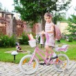 Stock Photo: Young school girl with pink backpack on a bicycle
