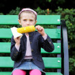 Pretty child girl eating a boiled corn outdoors — Stock Photo