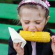 Pretty child girl eating a boiled corn outdoors — Stock Photo #6484640