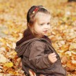 Beautiful baby girl plays in autumn forest — Stock Photo