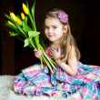 Portrait of adorable sunny child girl with tulips — Stock Photo #6485066
