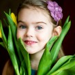 Stock Photo: Portrait of adorable sunny child girl with tulips