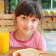 Amazed child girl has a breakfast outdoors — Stock Photo
