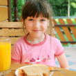 Amazed child girl has a breakfast outdoors — Stock Photo #6485188
