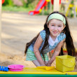 Happy child girl is playing in a sandbox — Stock Photo