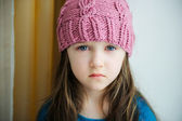 Adorable sad child girl in pink knitted hat — Stock Photo